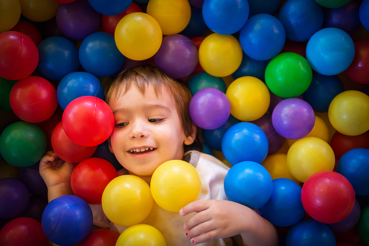 Young child smiling in a colorful ball pit.