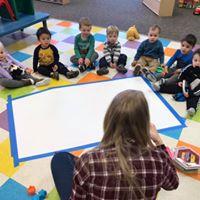 Young children sitting on the floor listening to teacher.